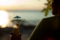 Man relaxing overlooking the ocean with a cocktail in his hand watching the tropical sunset